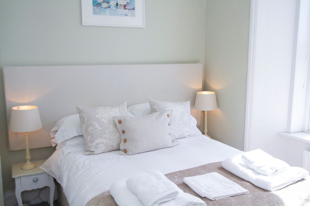 Our Tolcarne room with a double bed and light green walls