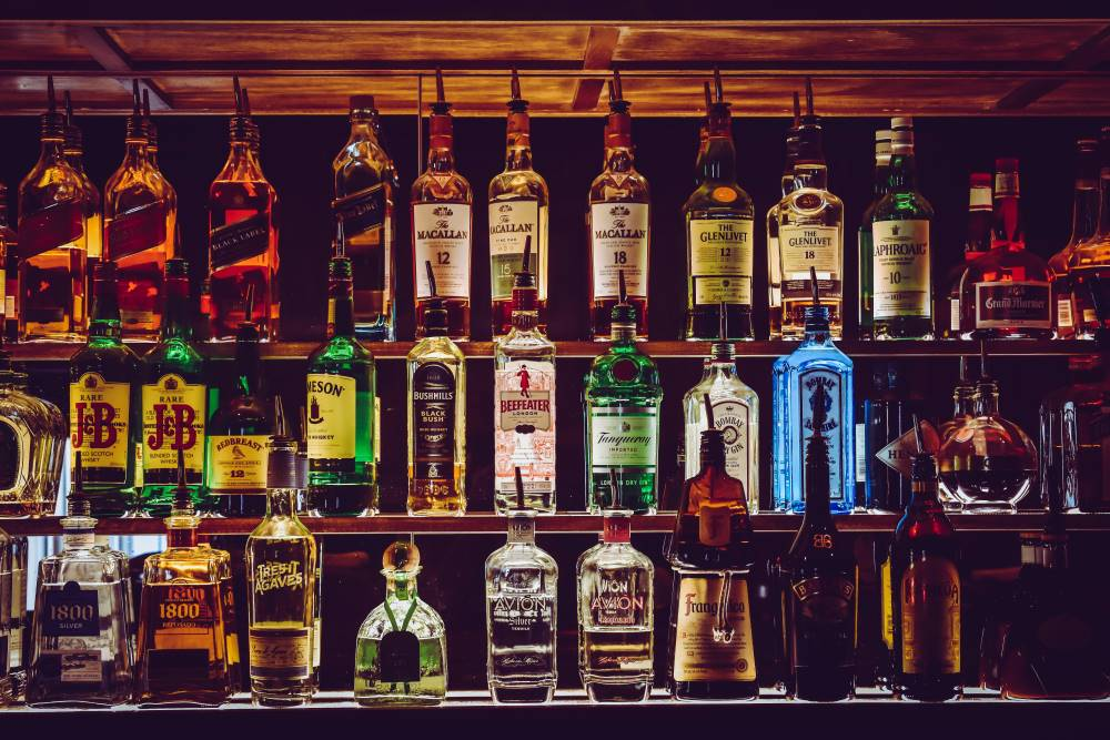 Out for drinks - Bottles of spirits lined up on a shelf behind the bar