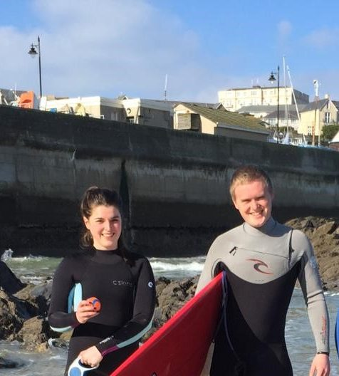 Hosts Dom and Rhia on the beach with surfboards