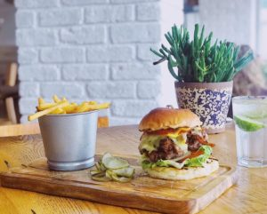 Burger and chips on a wooden table with a plant in the background