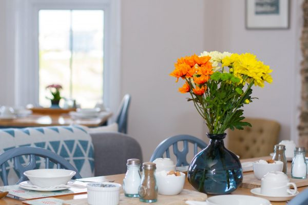 Orange and yellow flowers on table in Breakfast room