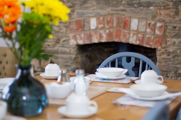 breakfast room table with log burner in the background