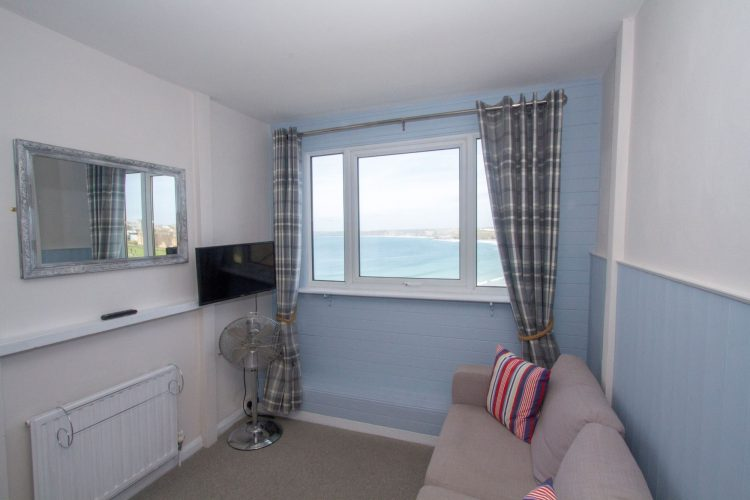Harbour View's view, pale blue walls with sea view outside of window