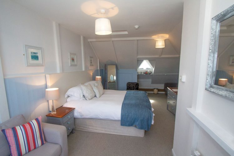 king size bed with white bedding in a stylish well lit room