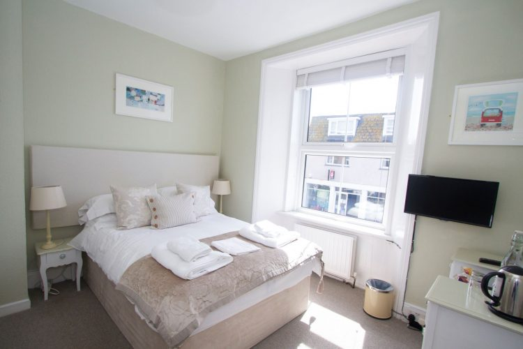small bright room with double bed and tv